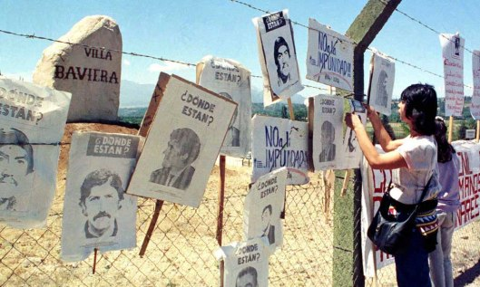 - UNDATED FILE PHOTO - A woman hangs up posters of missing people on  the fence surrounding the comp..